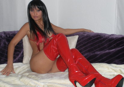 Long legged brunette MiLF shows off her curves in red thigh-high boots.